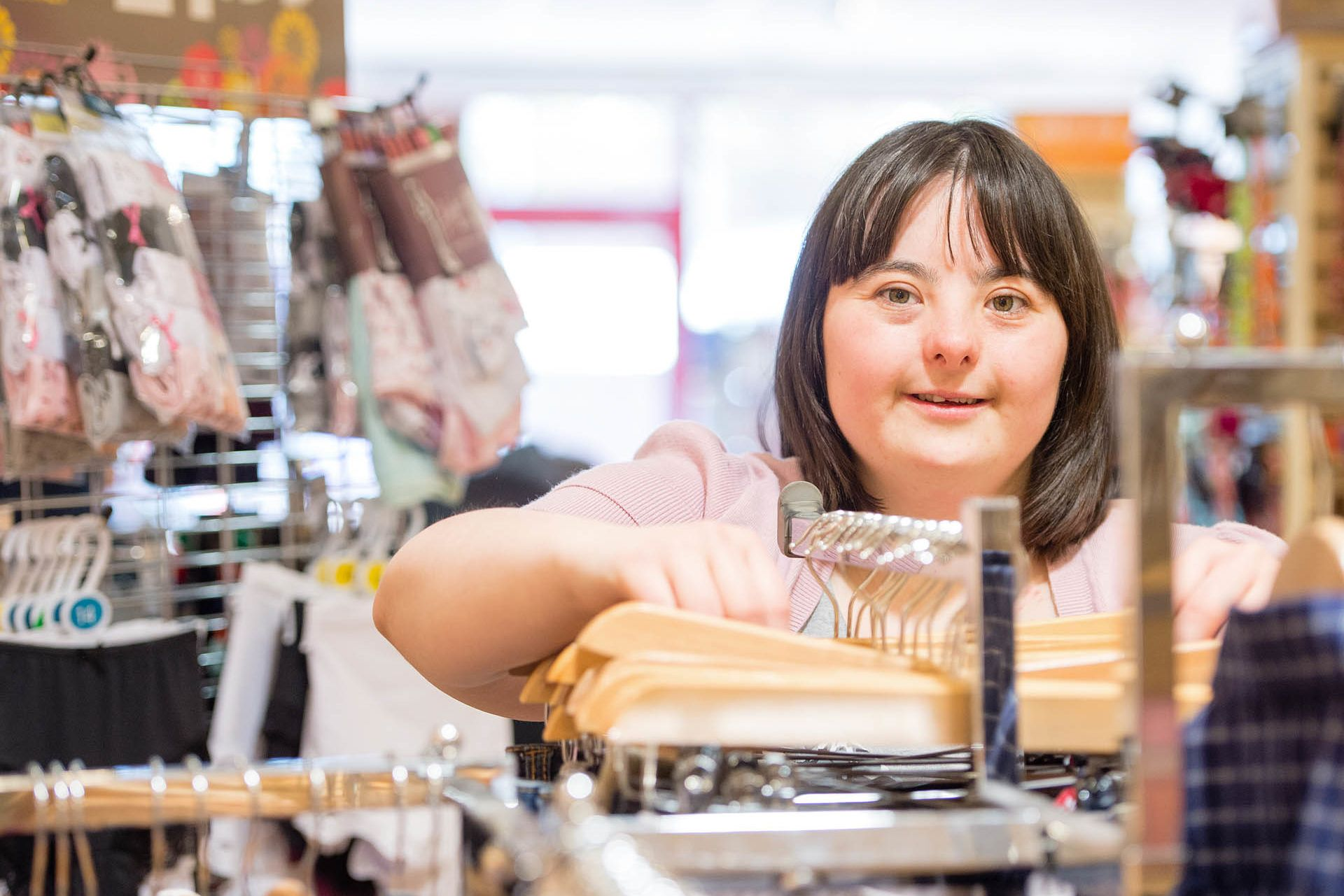 Woman with a learning disability sorting out clothes in a shop