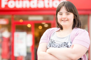 Young woman standing outside a British Heart Foundation shop