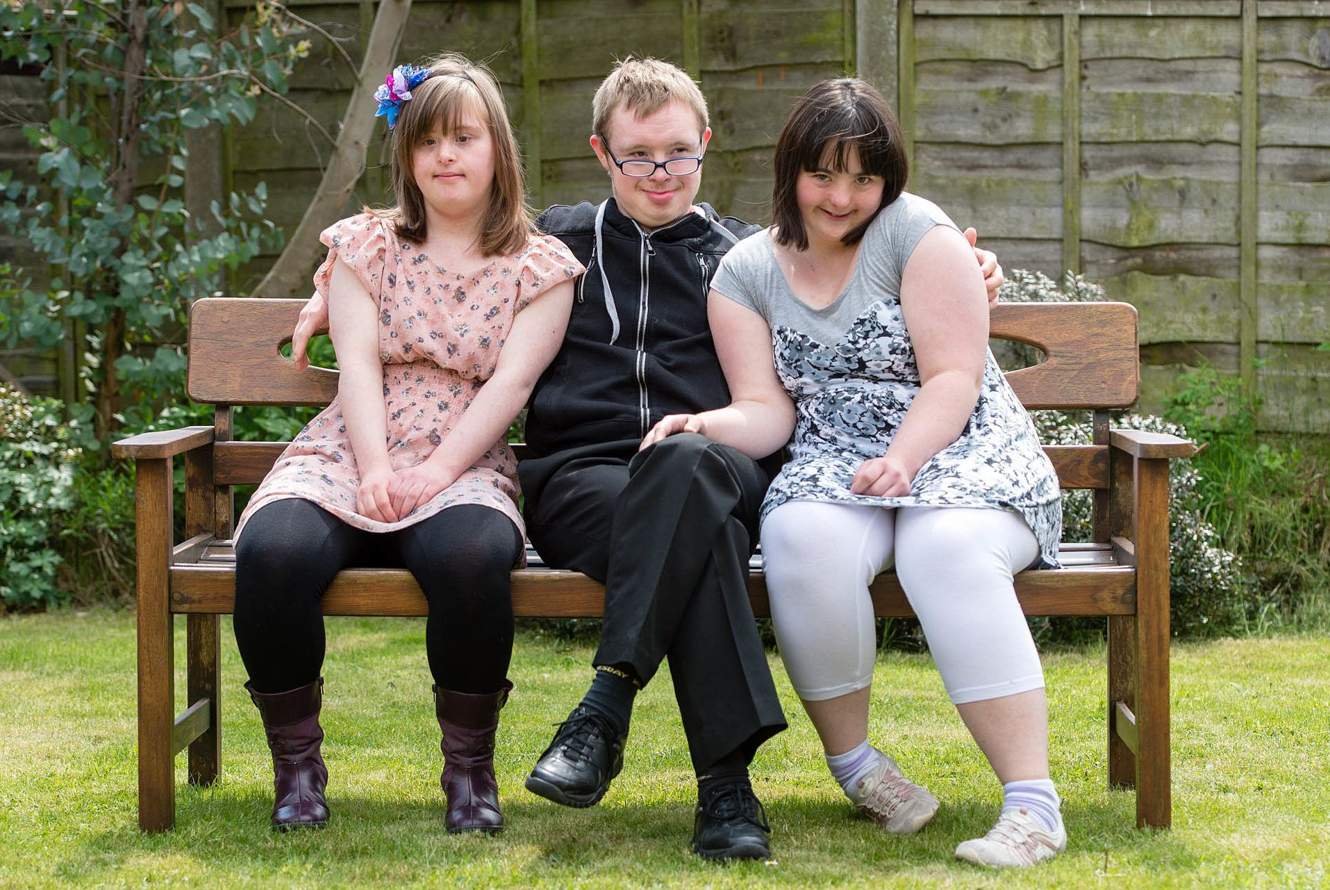 Two young women and one young man sat on a bench in their garden