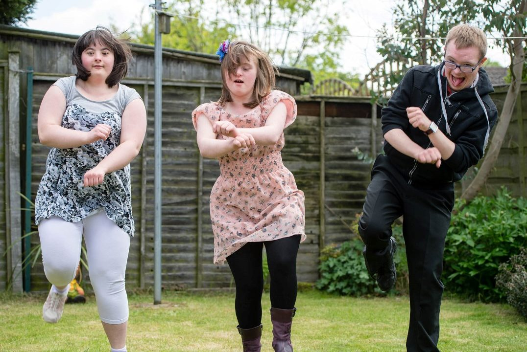 Two young women and a young man dancing in their garden