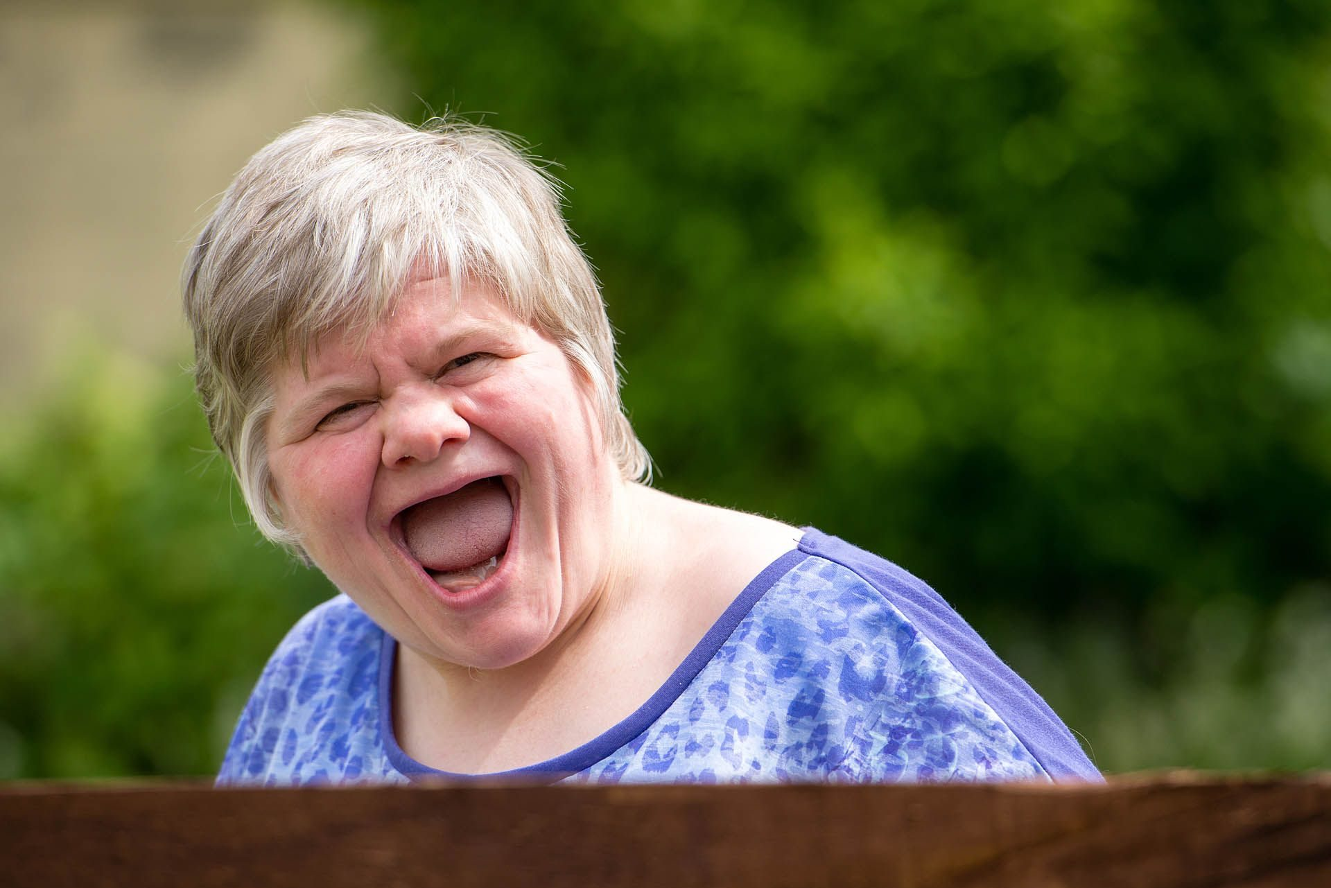 Woman with learning disabilities smiling at the camera