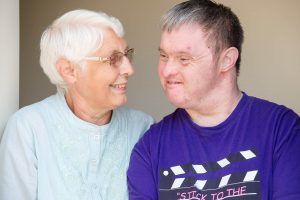A man in a purple t-shirt and a lady with glasses smiling at each other