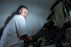 Man wearing headphones playing drums