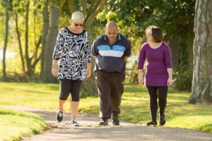 Two women and a man walking in the park
