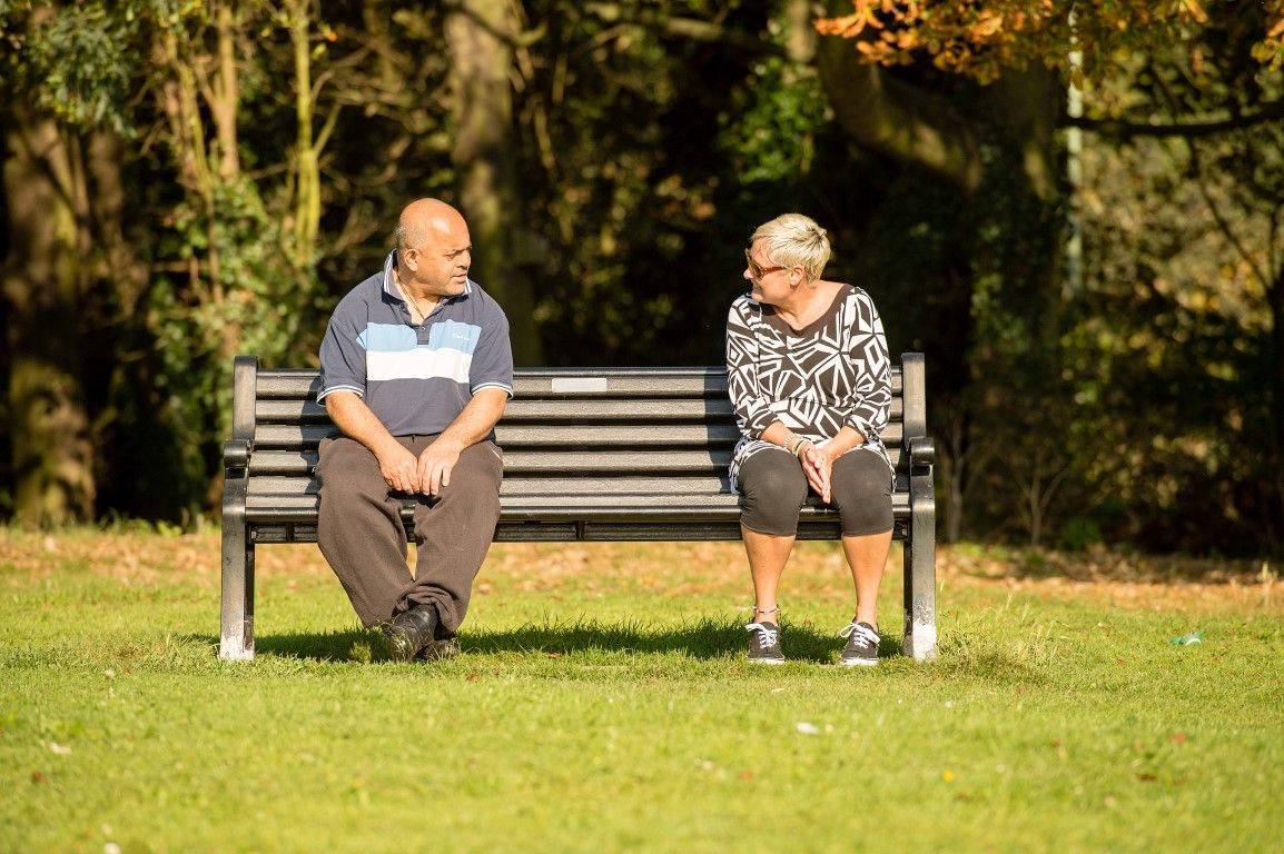 Man with a learning disability sitting on a benc with a woman
