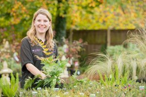 Woman in a polo shirt smiling, next to some plants