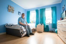 Man with learning disabilities sitting on his bed