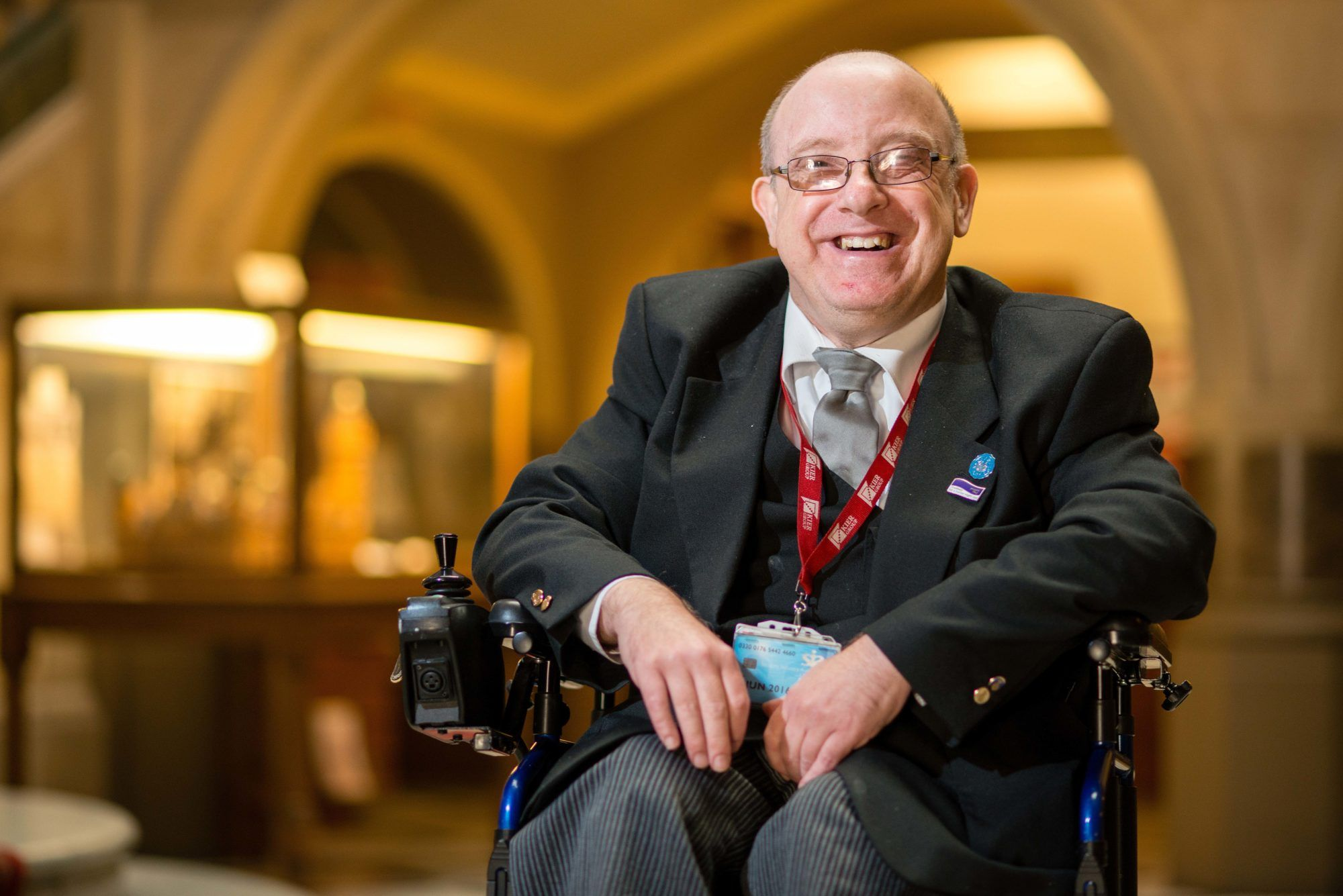 A man wearing glasses wearing a suit and smiling in a wheelchair