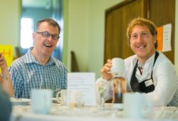 Two men with learning disabilities, sitting at a table and drinking tea