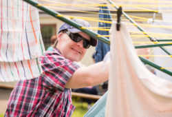 A man wearing sunglasses hanging his washing out