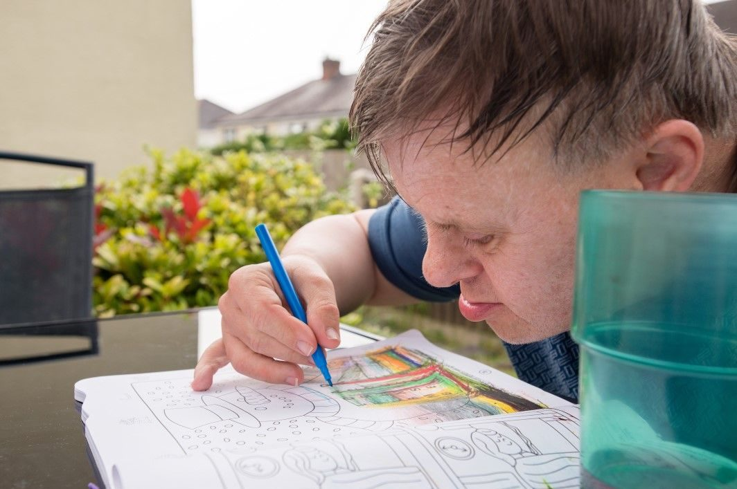 Man with learning disabilities using a colouring book