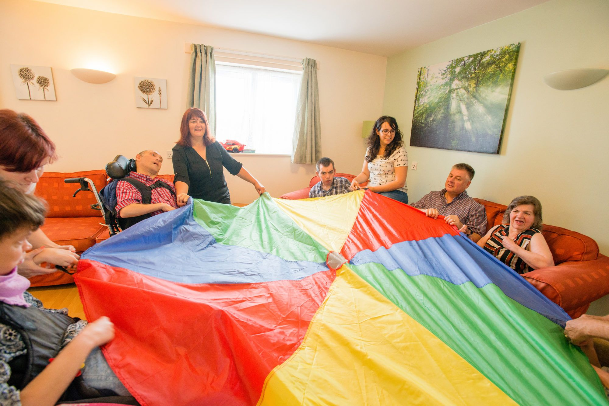 A group of people holding a multi-coloured parachute