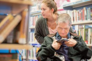 Man in wheelchair looking at a video, with a woman standing behind him