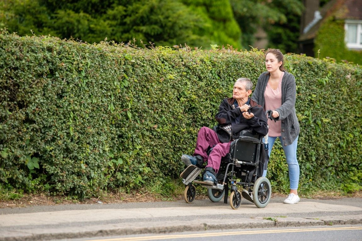 Woman pushing a wheelchair with a man in it, on a pavement
