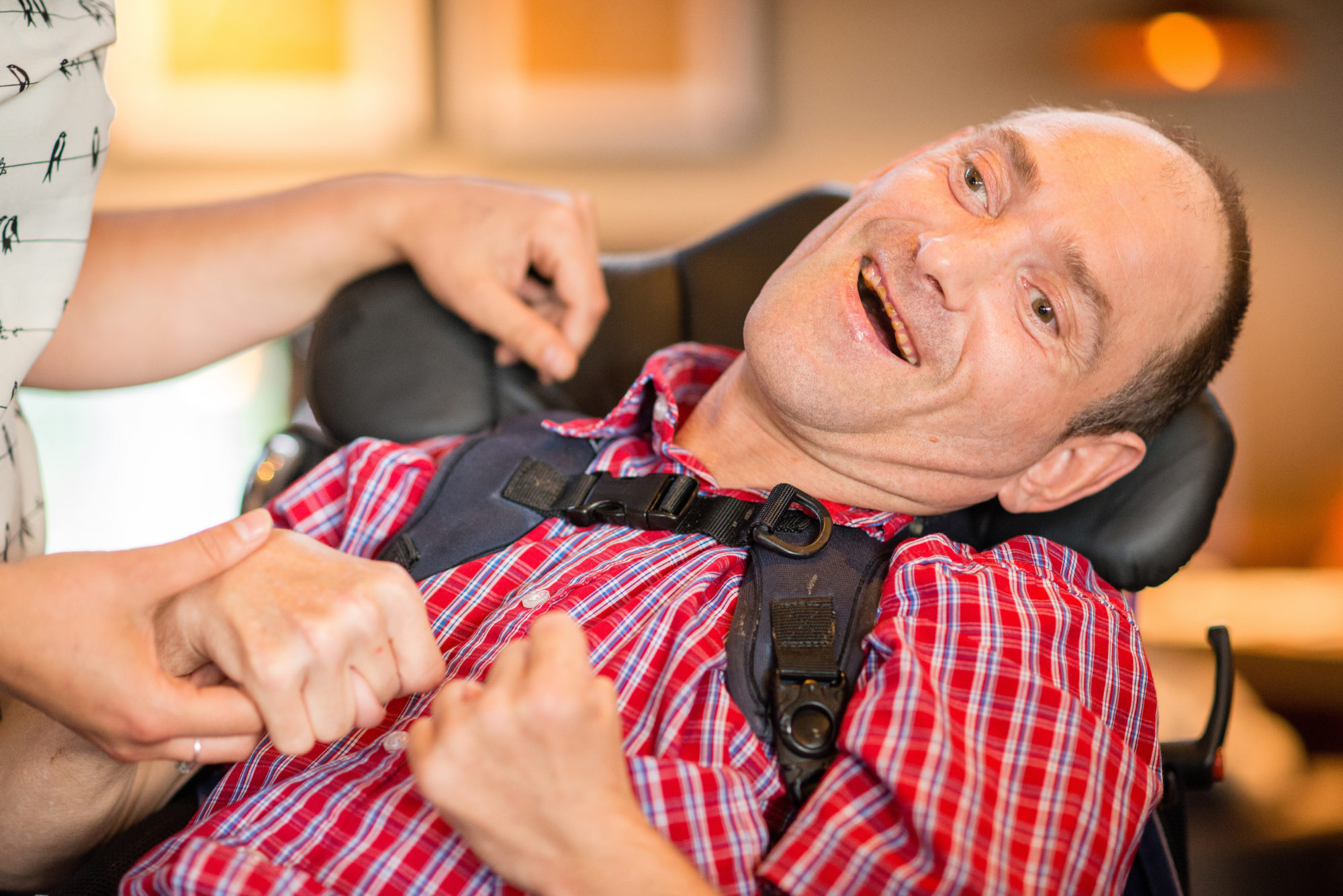 A man in a red and blue checkered shirt smiling in a wheelchair