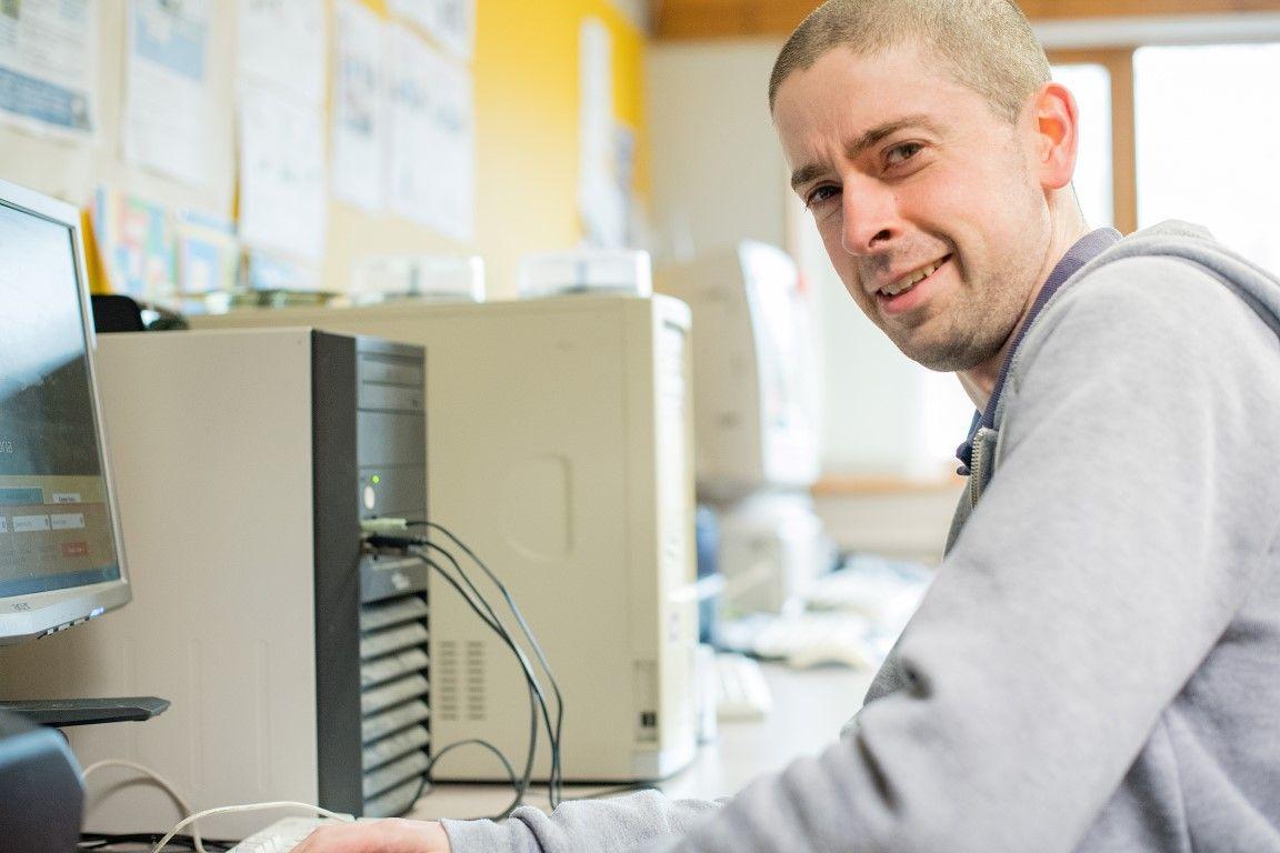 Man sat at a computer, smiling