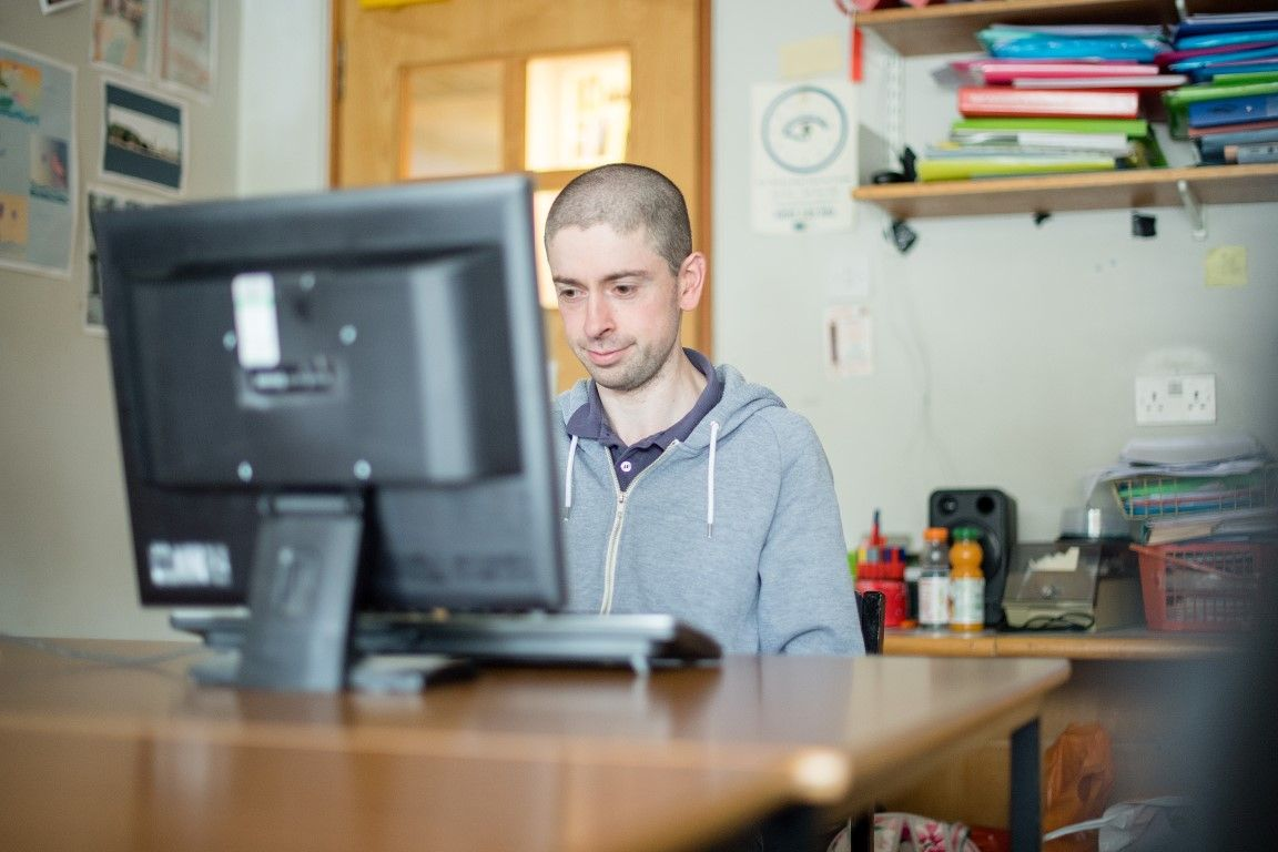 Young man with learning disabilities looking at his computer