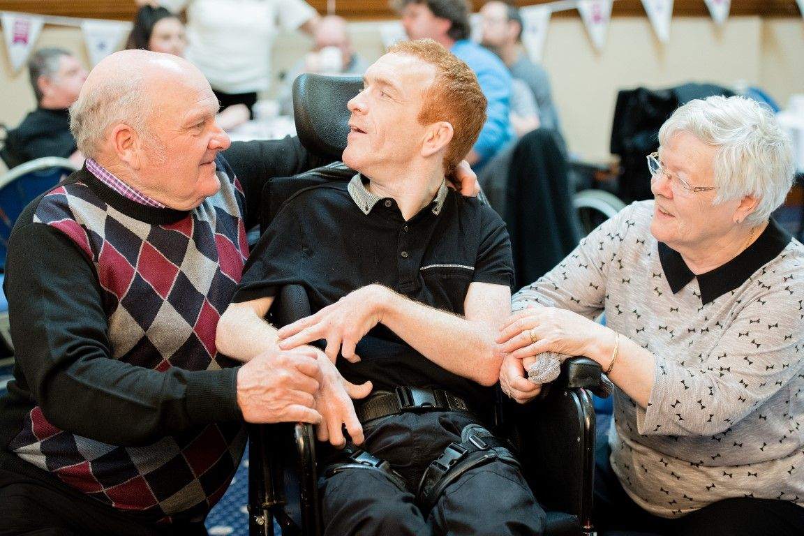 A man in a wheelchair with his father on the left and his mother on the right