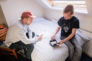 Two men sat on a bed with a moneybox