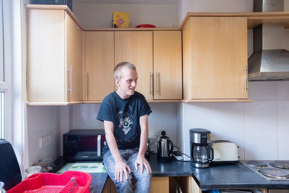 Man sitting on a kitchen work surface