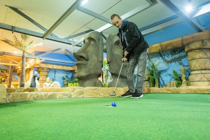 Young man playing indoor golf