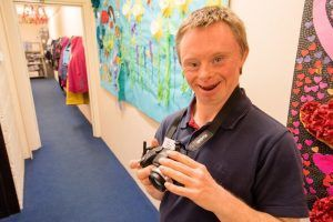 Man with learning disabilities holding a camera