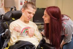 Young woman in a wheelchair with another woman smiling at her