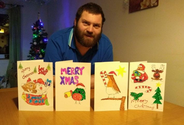 Man with Christmas cards he designed himself