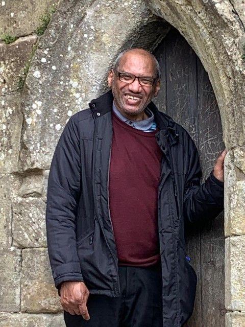 Man in anorak next to a castle door