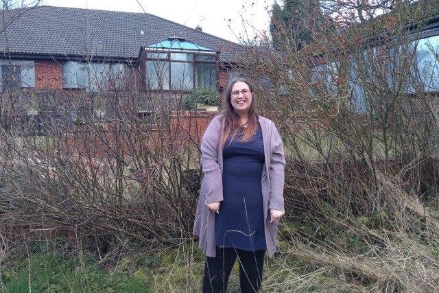 Woman standing in an overgrown garden