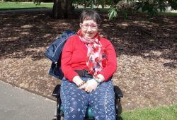 Woman in wheelchair in front of a tree