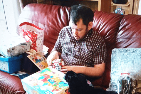 Young man opening Christmas presents