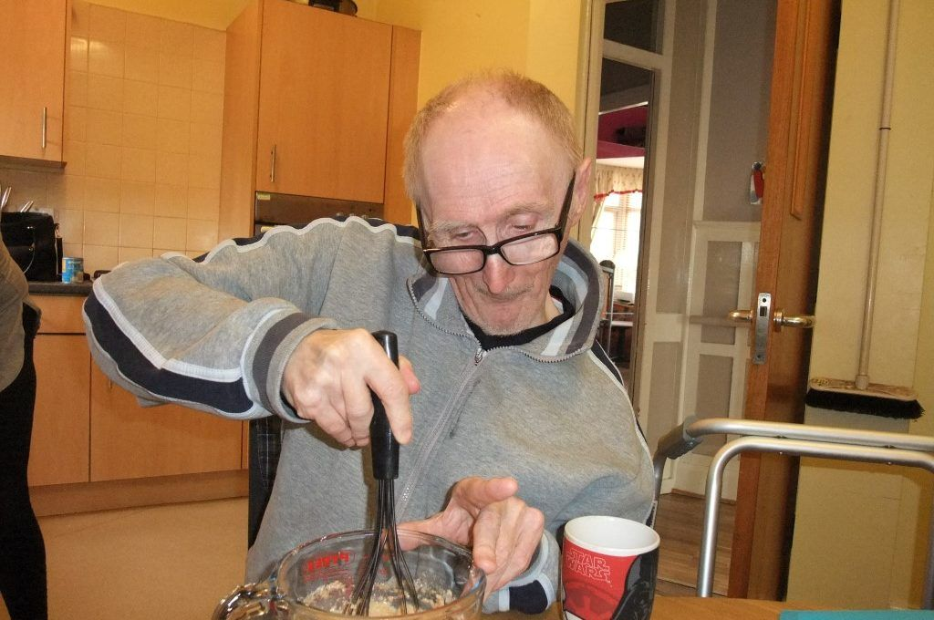 Man with glasses mixing food in his kitchen
