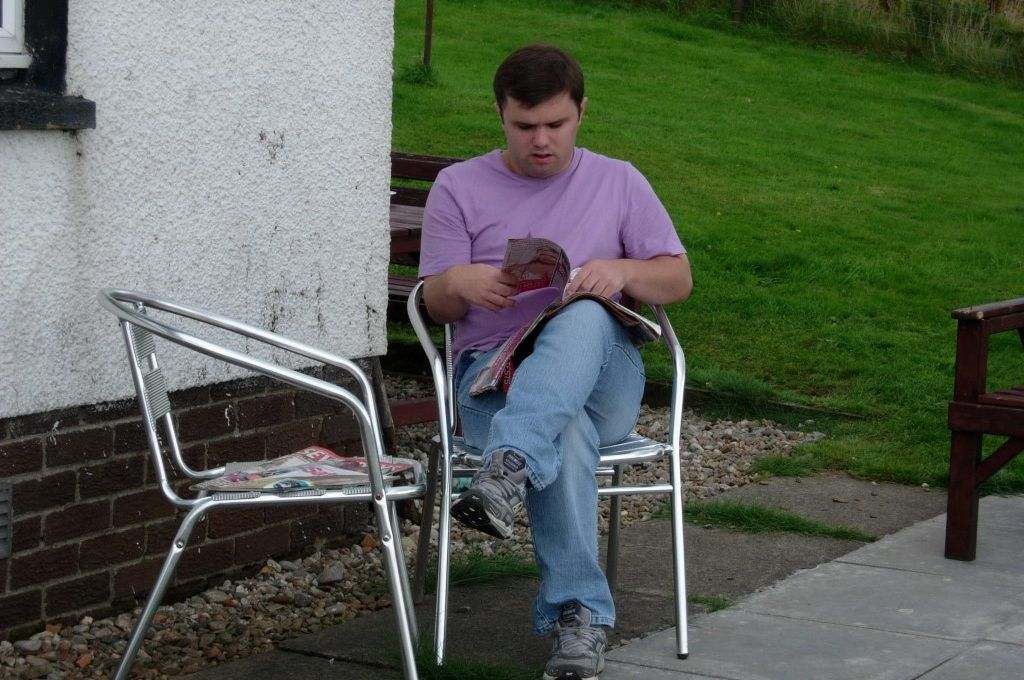 Man with learning disabilities reading outside his house
