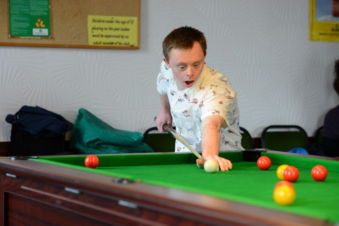 Young man with learning disabilities playing pool