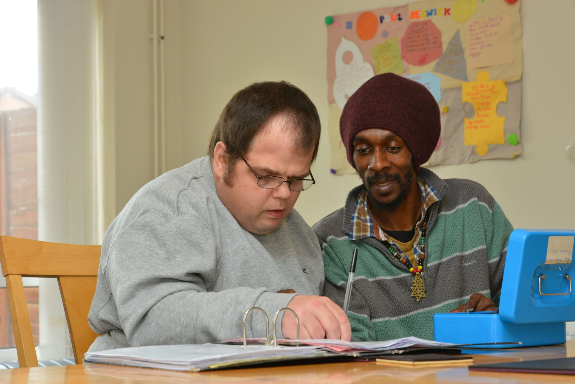 Two men at a table, one is writing in a file