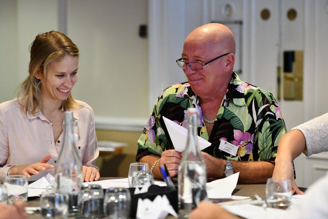 Woman and man sat at a table at a charity conference