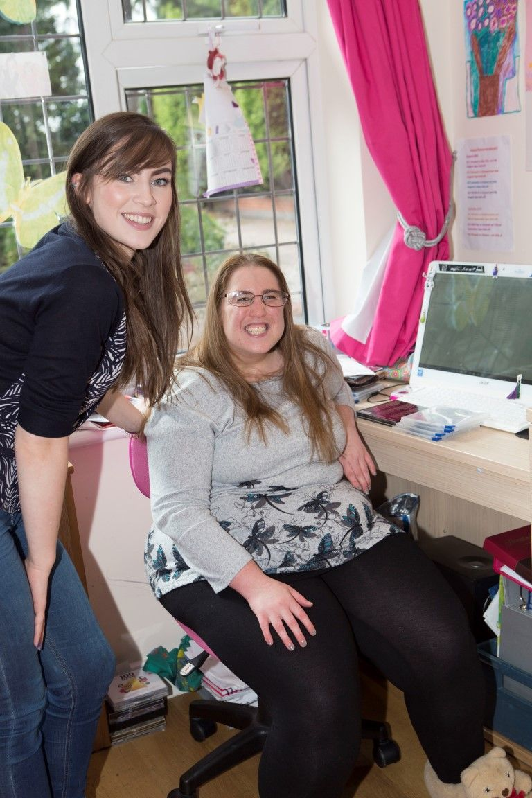 Woman sitting at her computer, smiling, wth a woman stood next to her