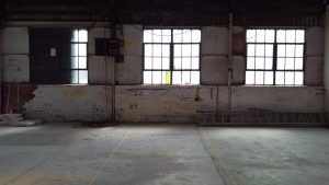 An empty warehouse with three windows