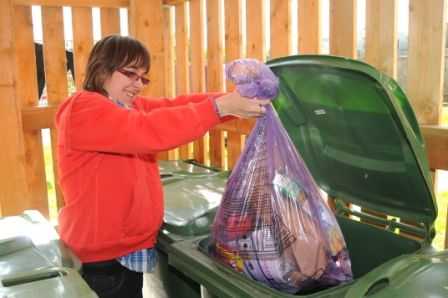 Woman with learning disabilities putting a rubbish bin into a skip