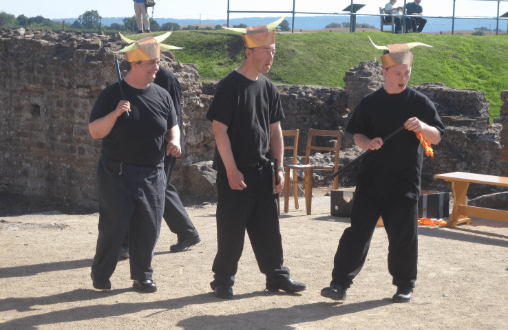 Three actors with learning disabilities wearing black clothes and funny hats
