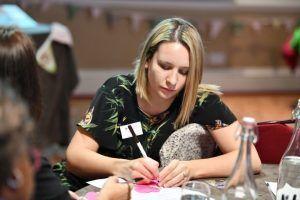 Woman sat at a table, writing