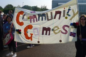 Two ladies holding a hand made community games banner
