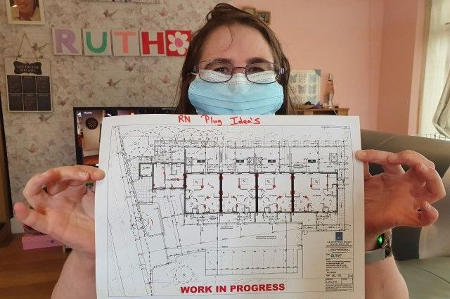 Woman holding up a floor plan
