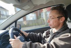 Man in glasses driving a car