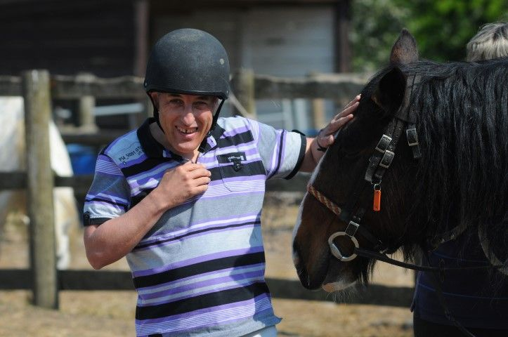 Man in riding hat patting a horse's head