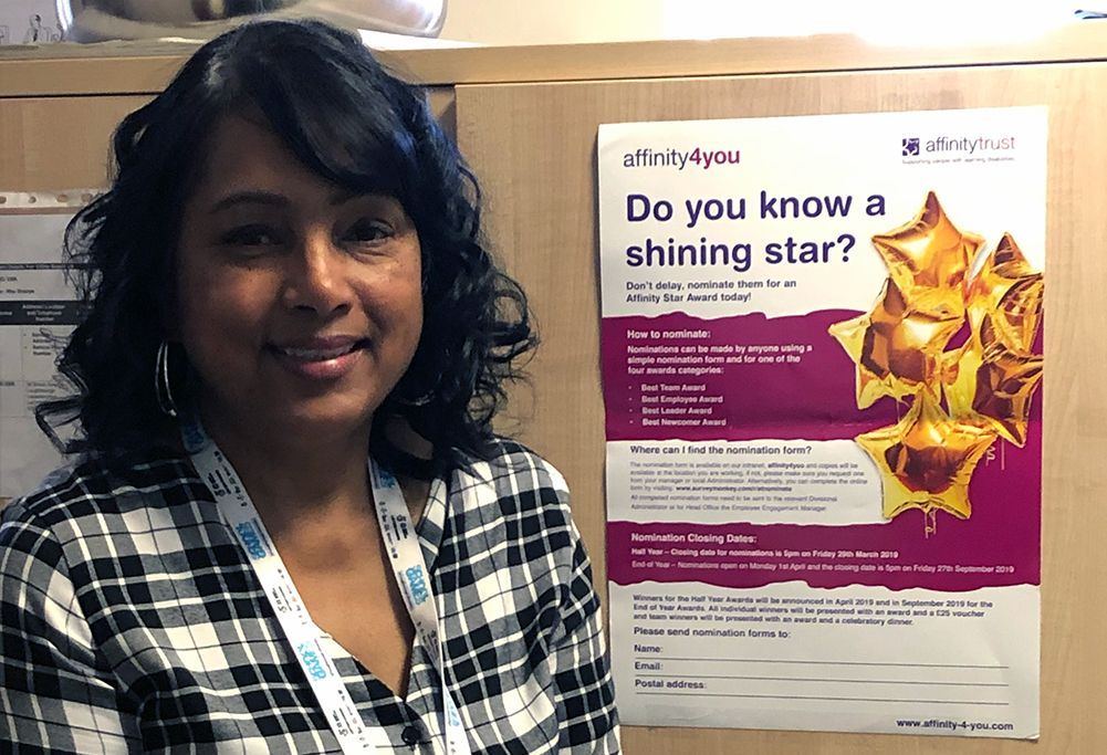 Woman standing next to an Affinity Trust poster