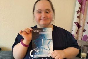 Woman holding a piece of paper saying Congratulations Tammy