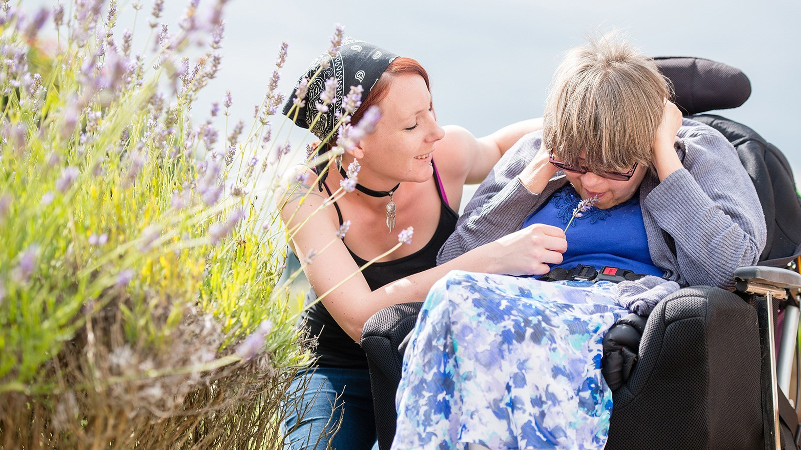 Woman showing woman in wheelchair some lavender