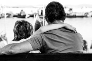 Boy with his arm around his father